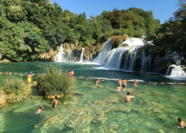 People in waterfall river pool during summer